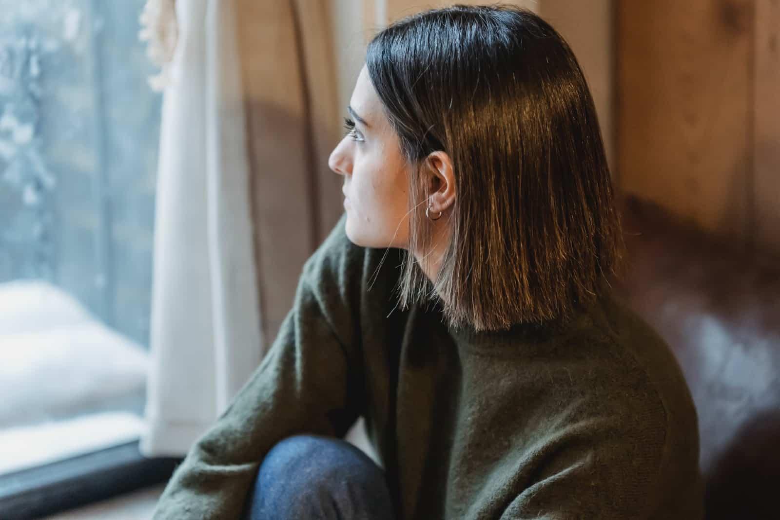 femme pensive en chandail brun regardant par la fenêtre