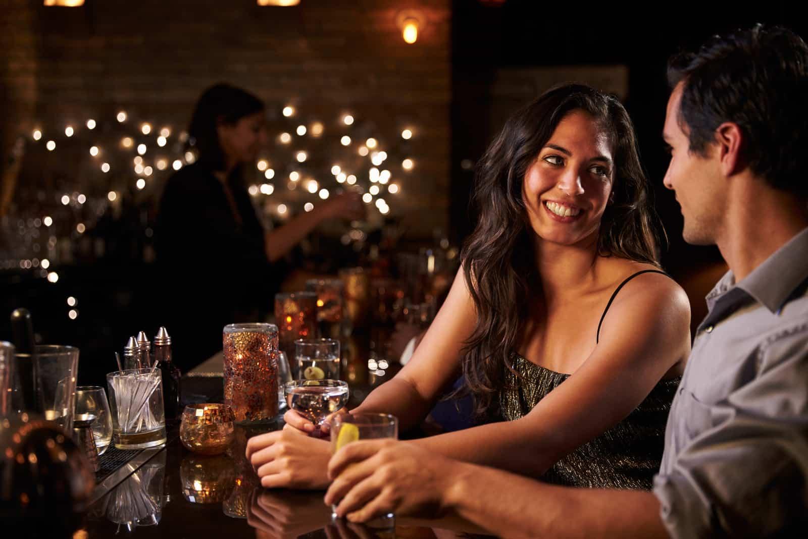 femme heureuse regardant un homme assis dans un bar