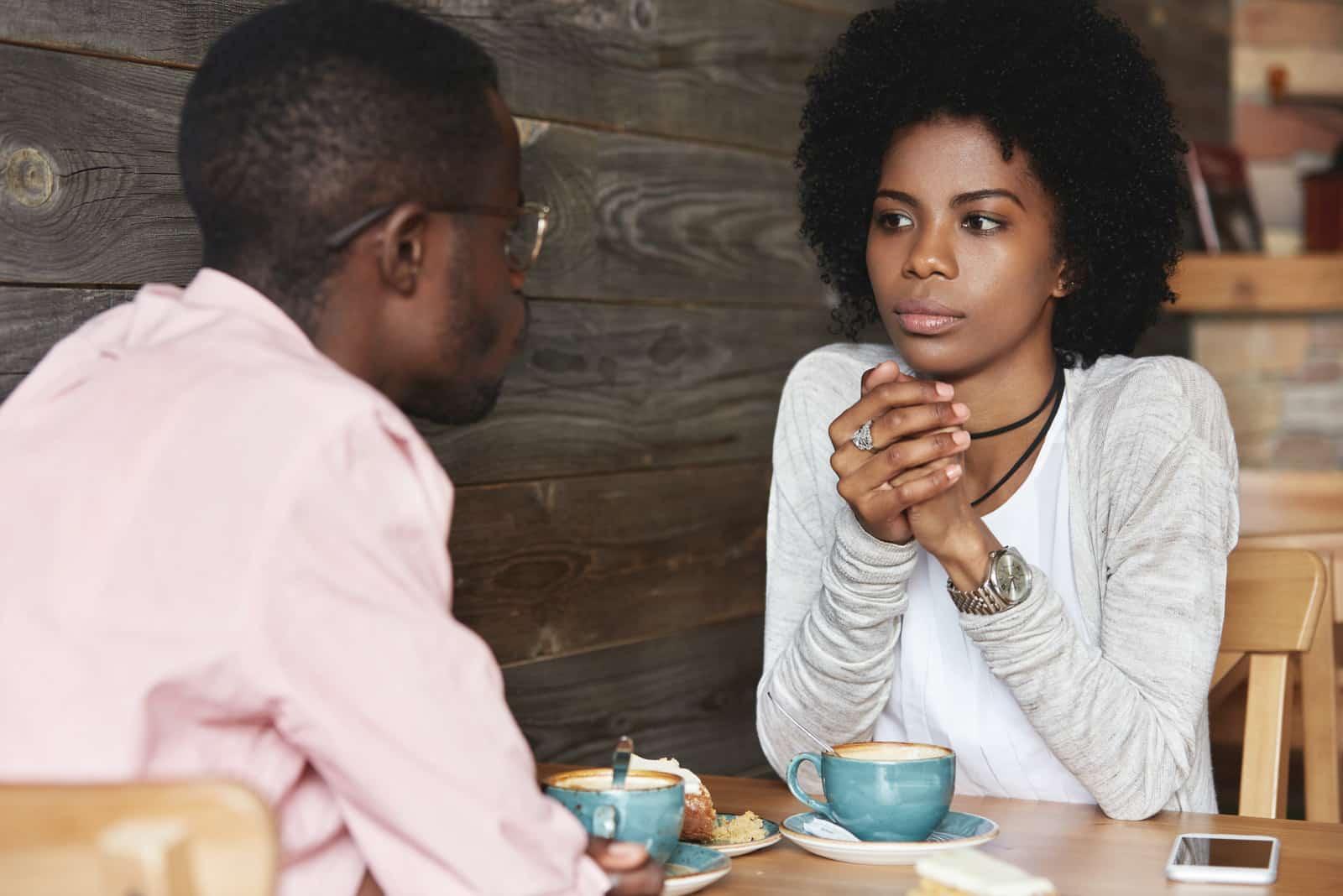 Une femme sérieuse regarde un homme assis dans un café.