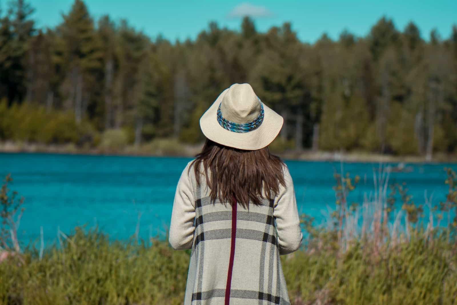 femme avec un chapeau regardant un lac