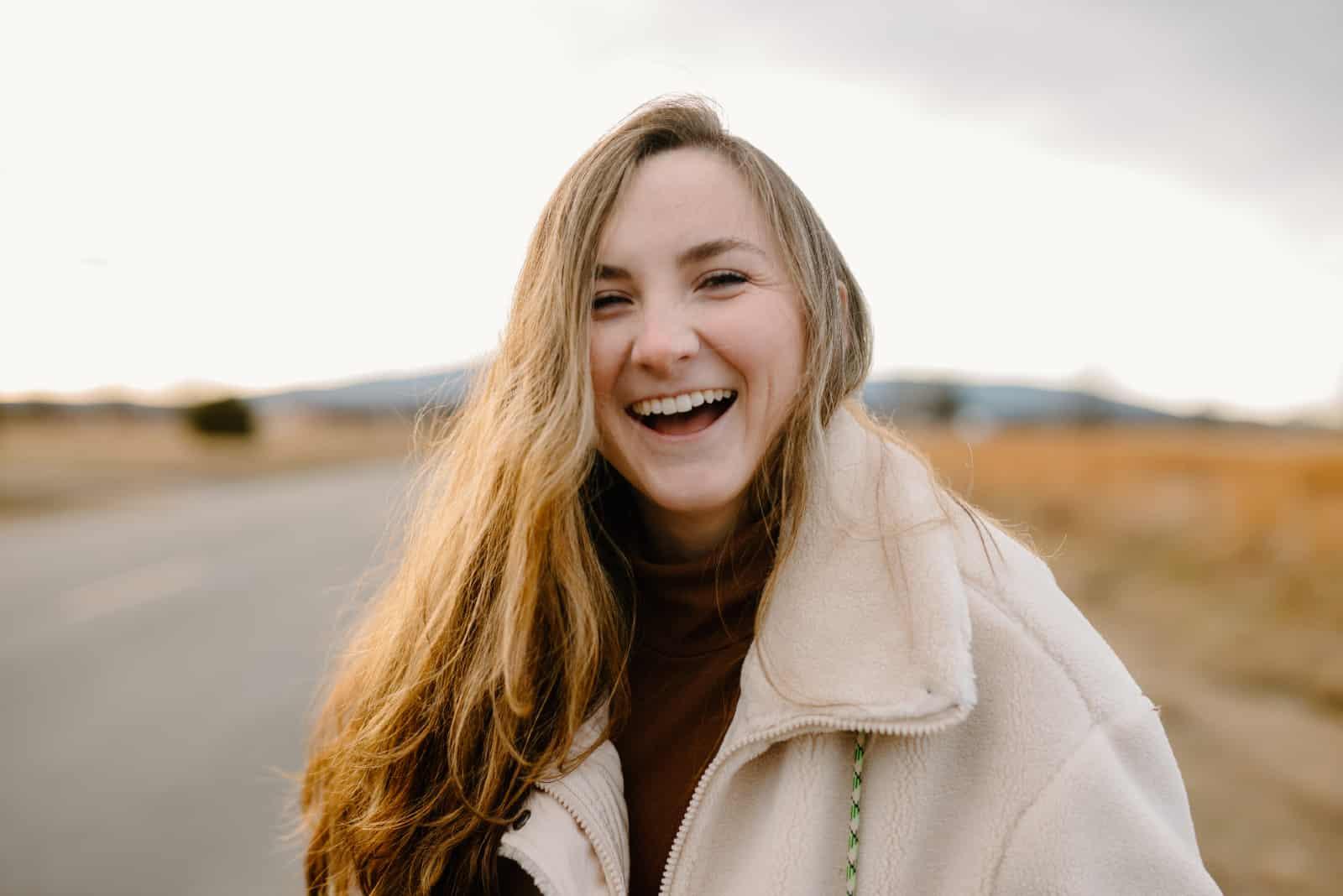 femme en veste blanche souriant en se tenant debout sur la route