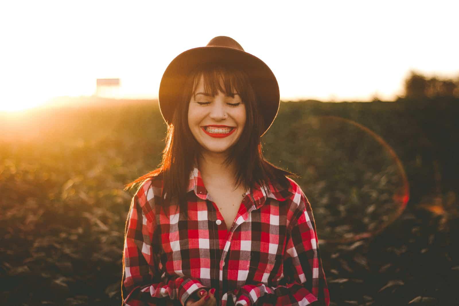 femme avec un chapeau souriant debout dans un champ