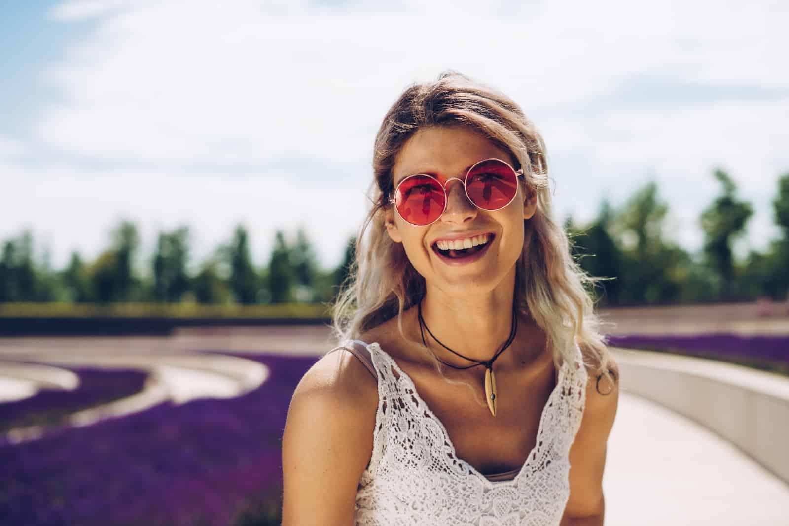 femme en haut de dentelle blanche souriant en plein air