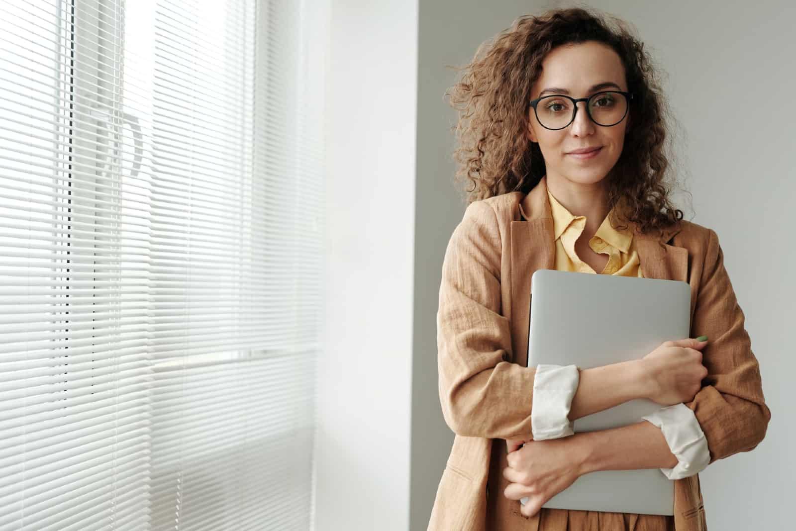 femme avec des lunettes tenant un ordinateur portable