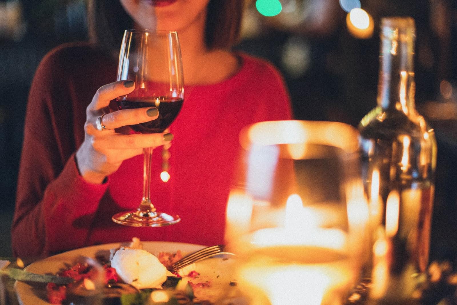 femme tenue verre vin quoique séance table