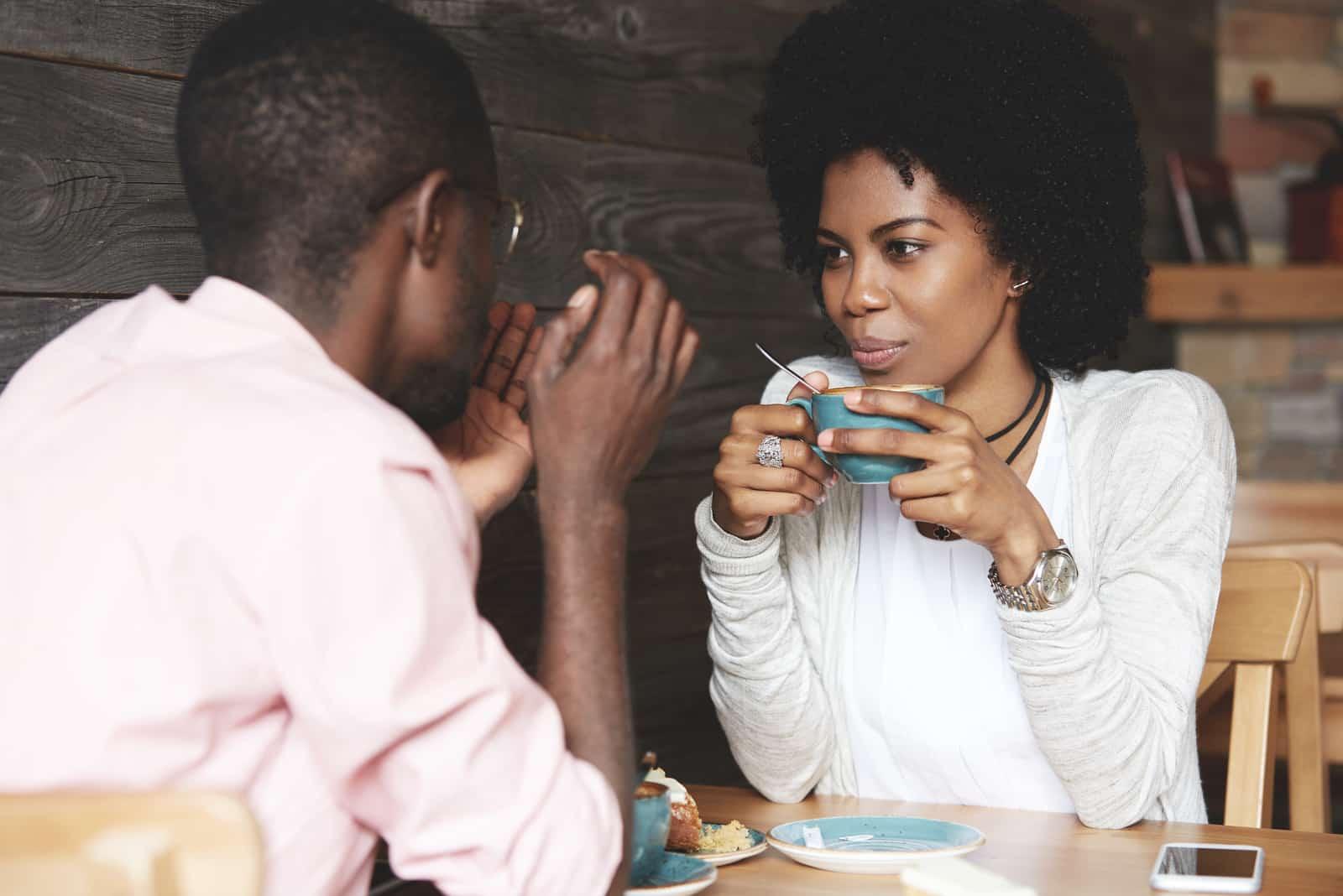 femme tenant une tasse de café, écoutant et regardant son petit ami
