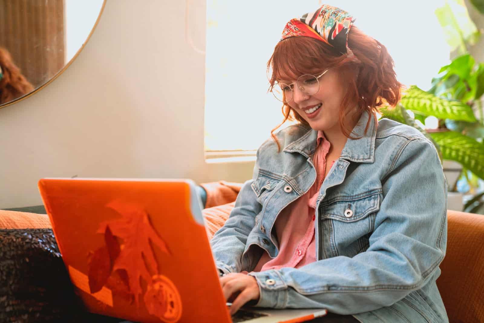 Femme heureuse utilisant un ordinateur portable, assise sur un canapé