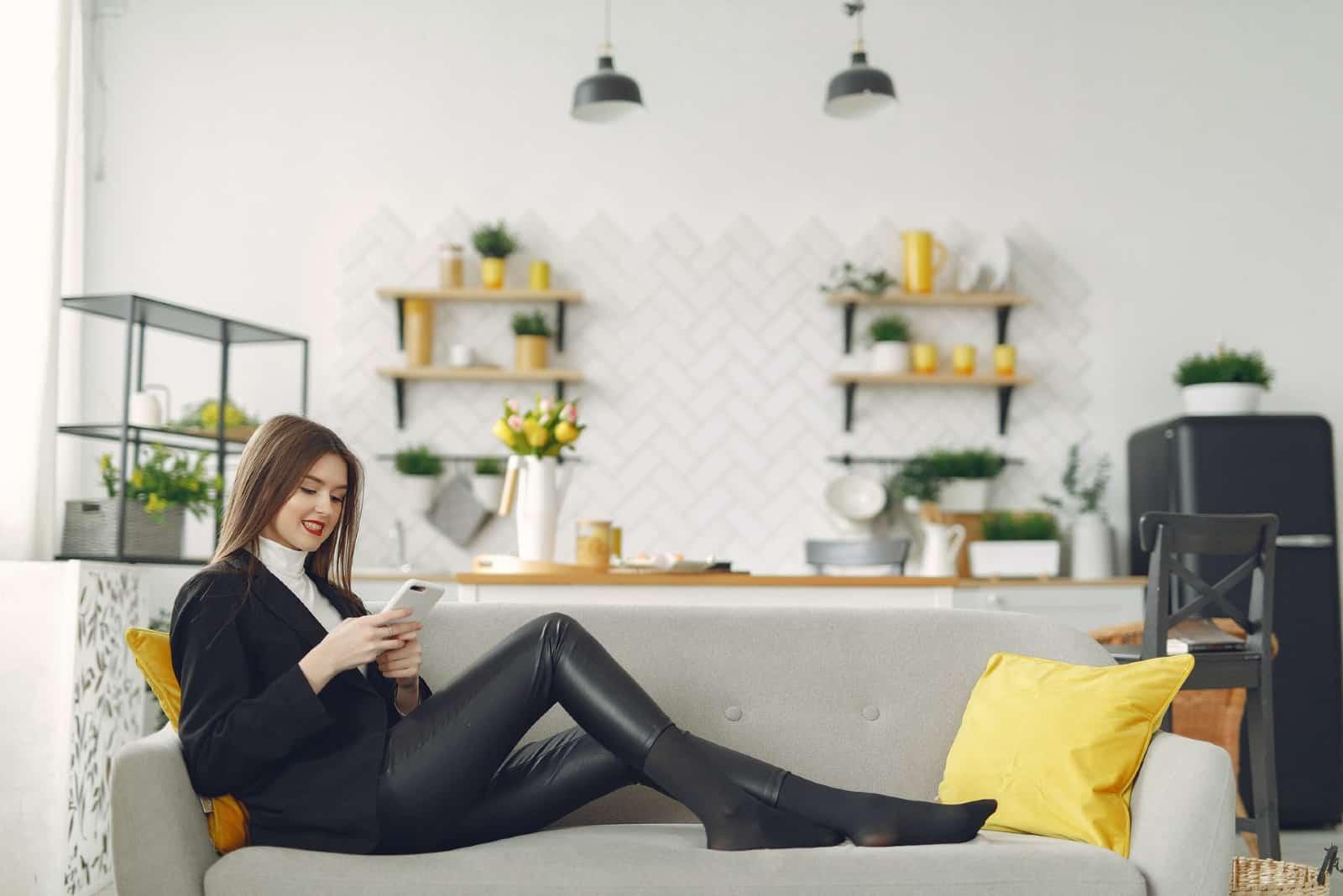Femme à l'aide de smartphone assis sur un canapé