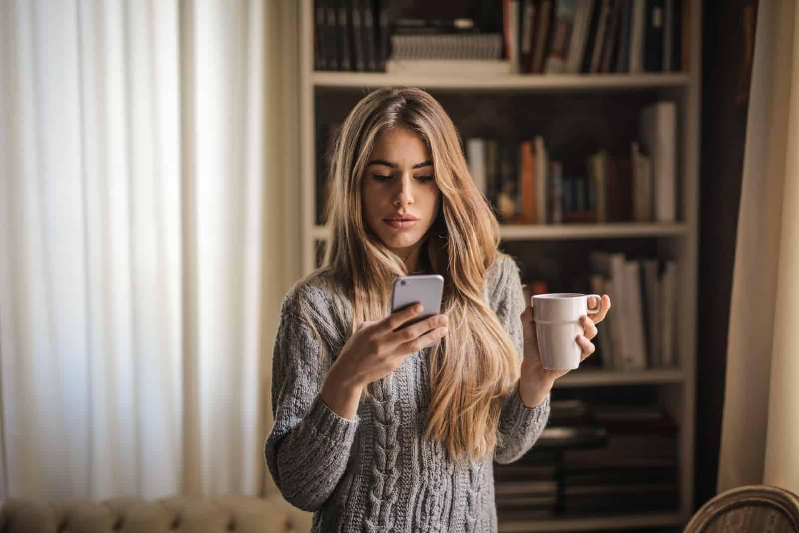 Femme utilisant un smartphone alors qu'elle est assise à l'intérieur