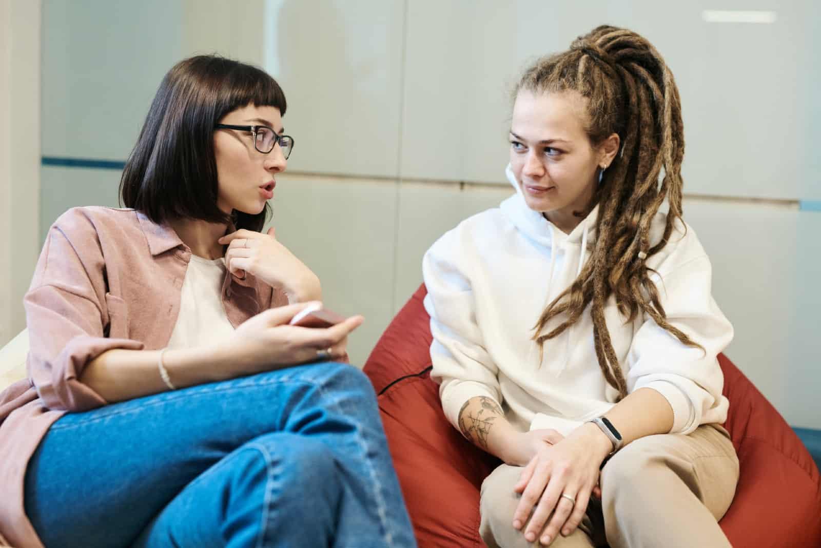 deux femmes discutant assises sur des sacs de repos