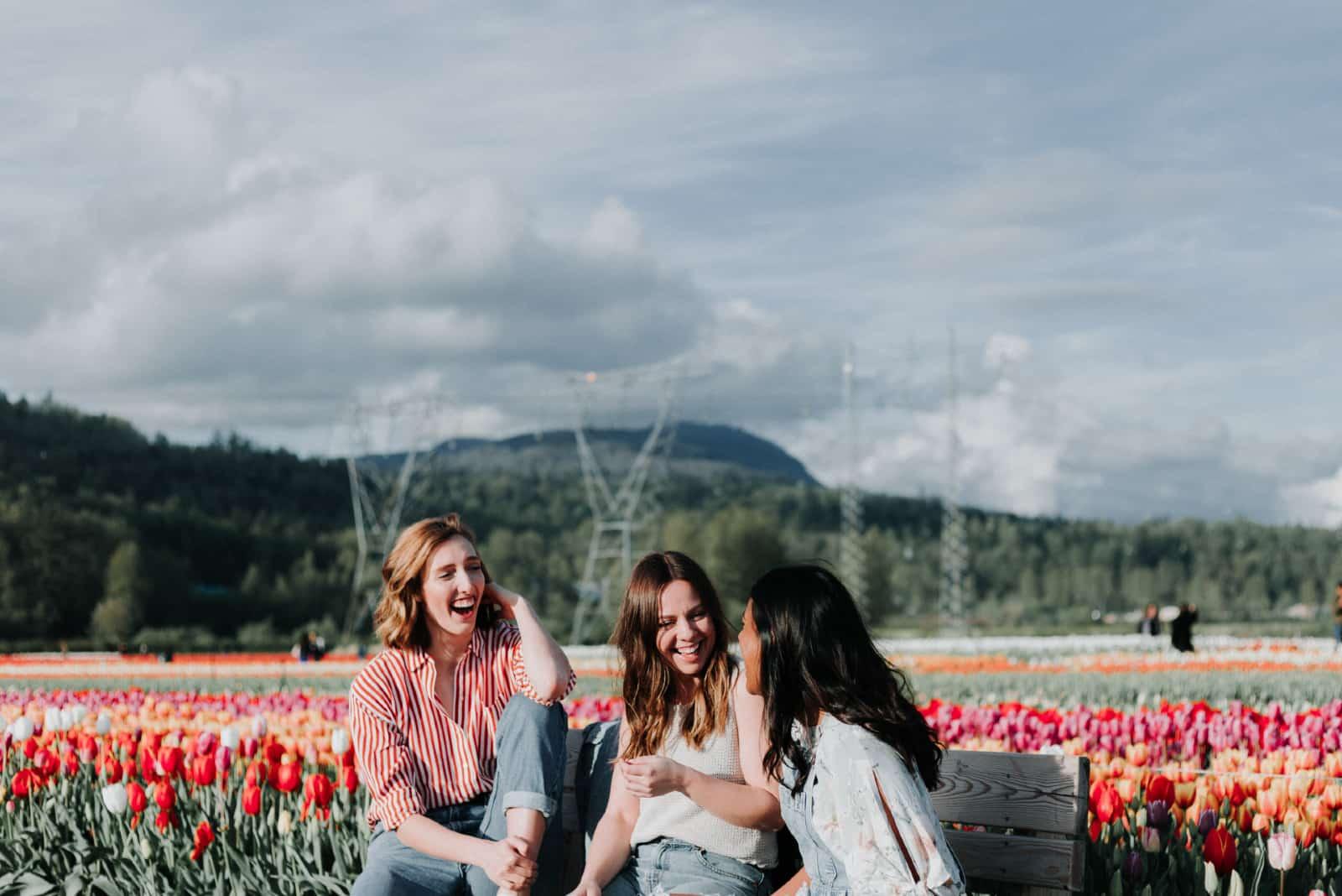 trois femmes souriantes assises sur un banc