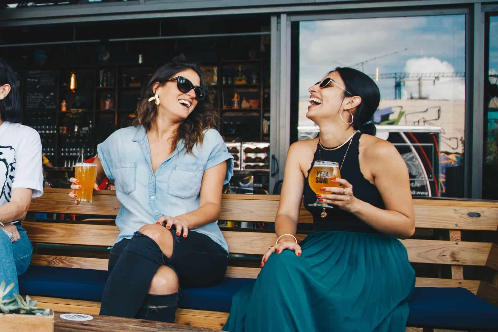 Deux femmes heureuses buvant de la bière assis sur un banc