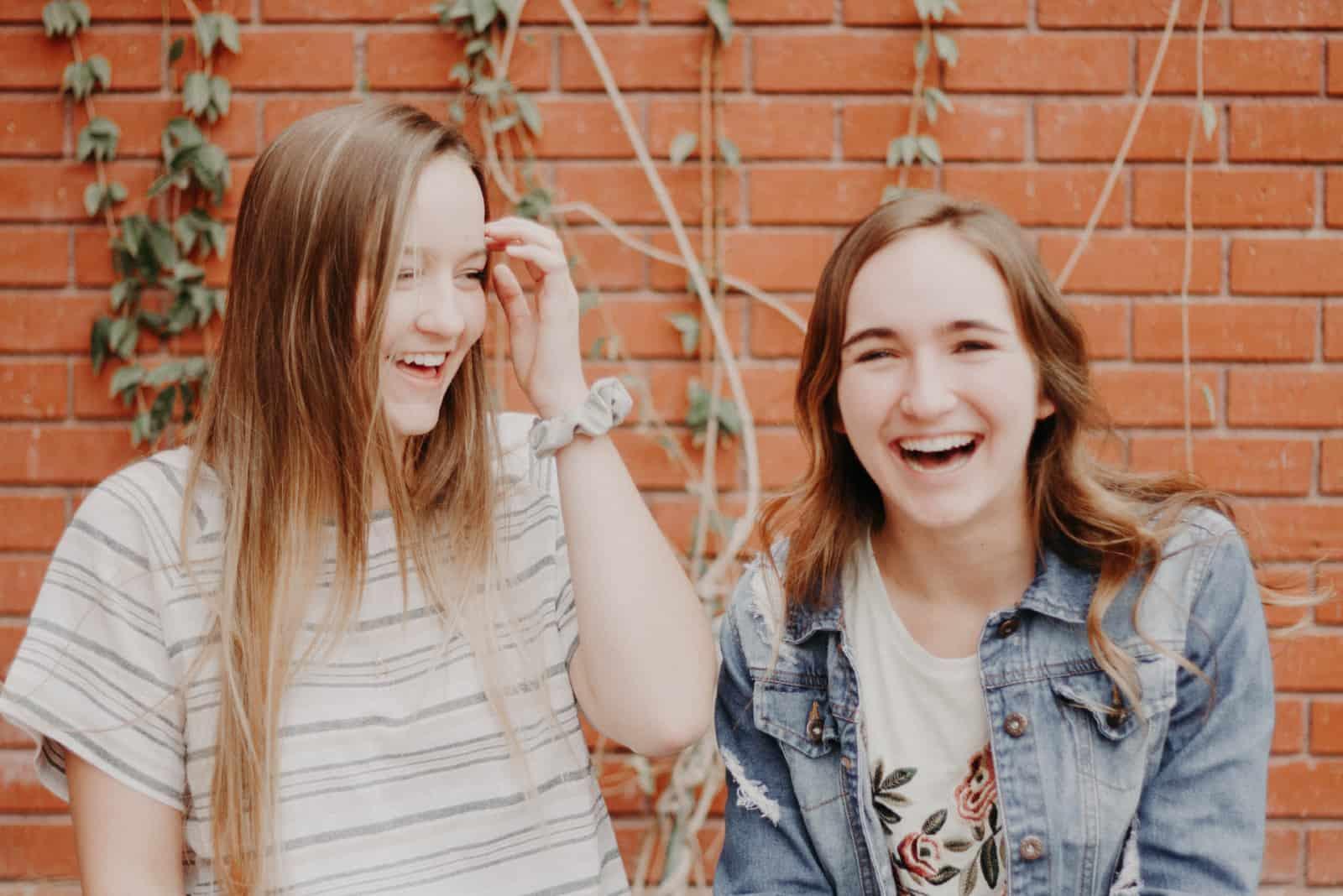 deux femmes sourient en se tenant près d'un mur