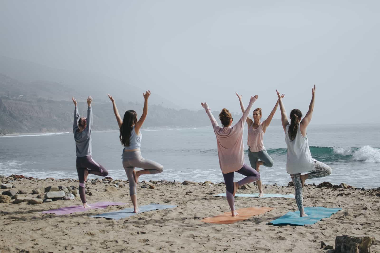 femmes faisant du yoga en se tenant debout au bord de la mer