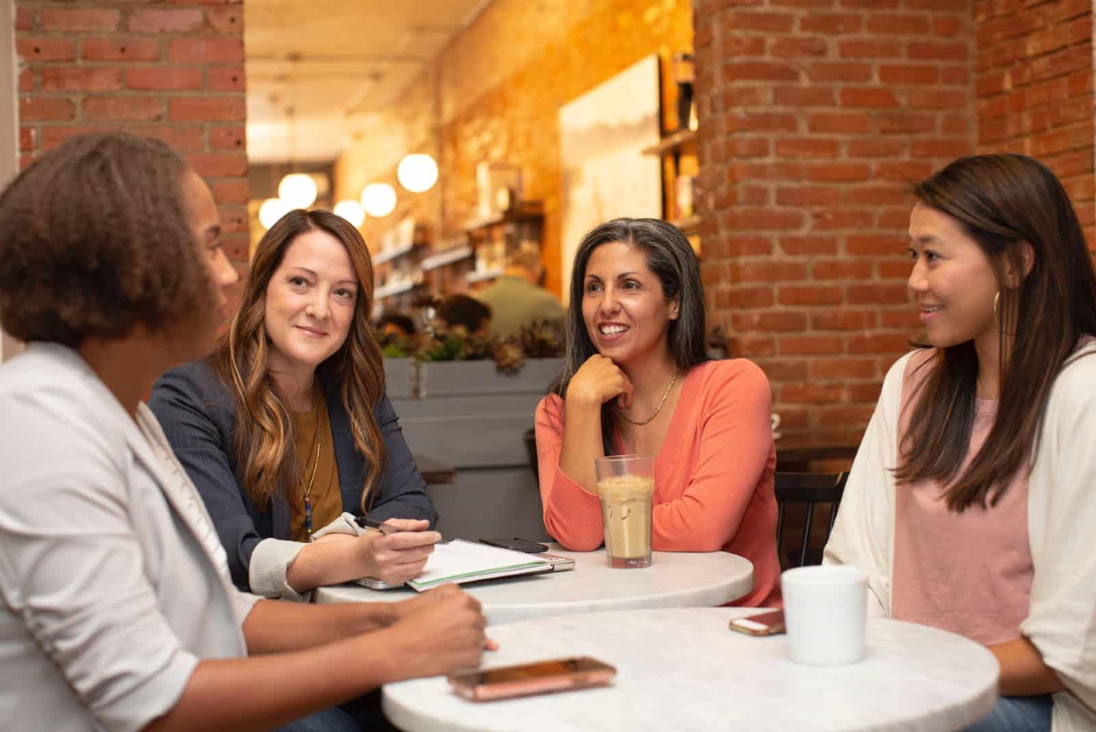 quatre femmes qui parlent assis dans un café