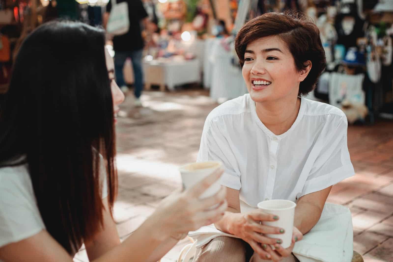 deux femmes qui parlent en chemises blanches parlent
