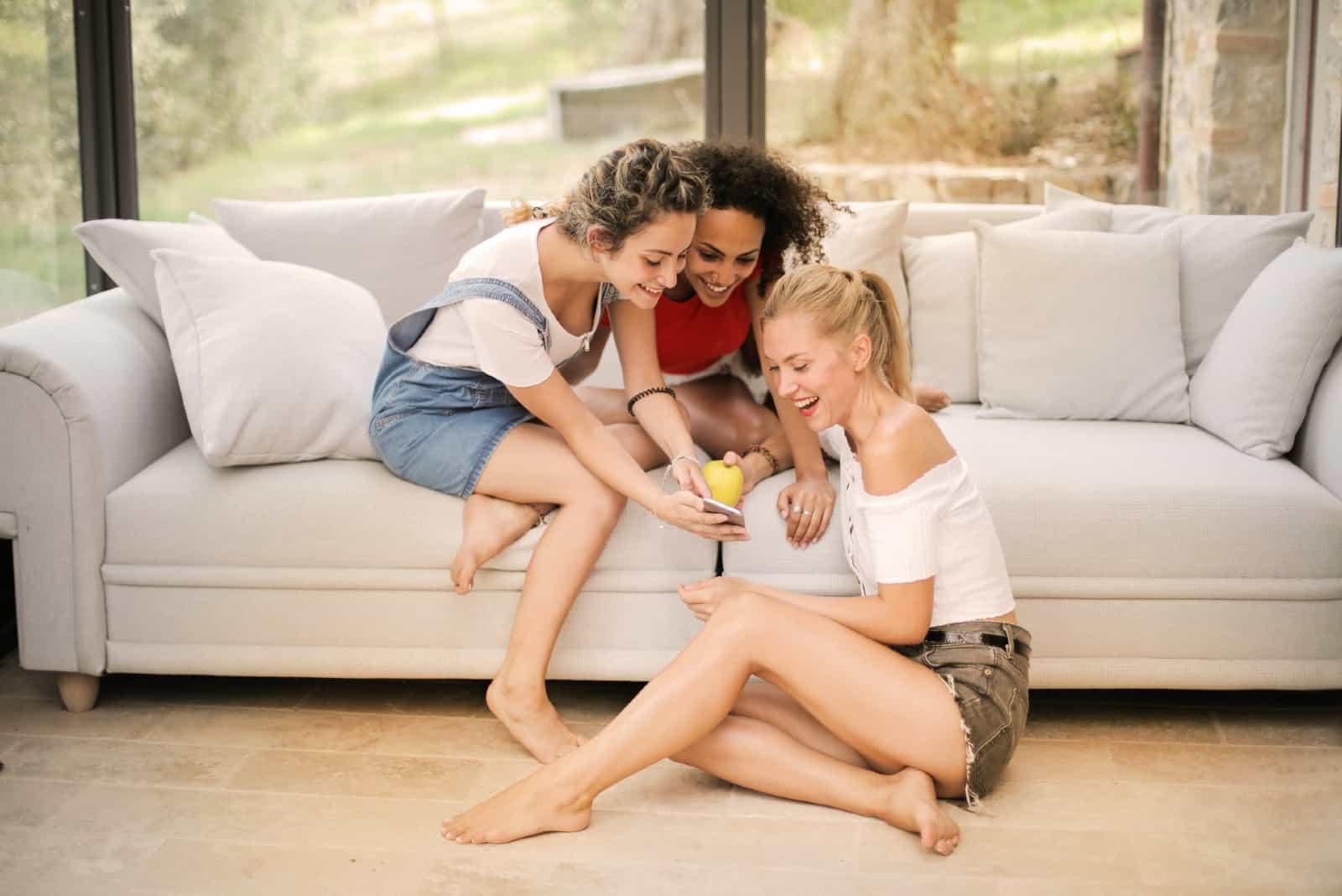 trois femmes regardant un smartphone en étant assises à l'intérieur