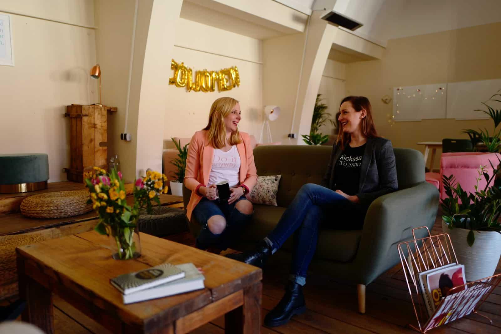 deux femmes sourient en s'asseyant sur un canapé