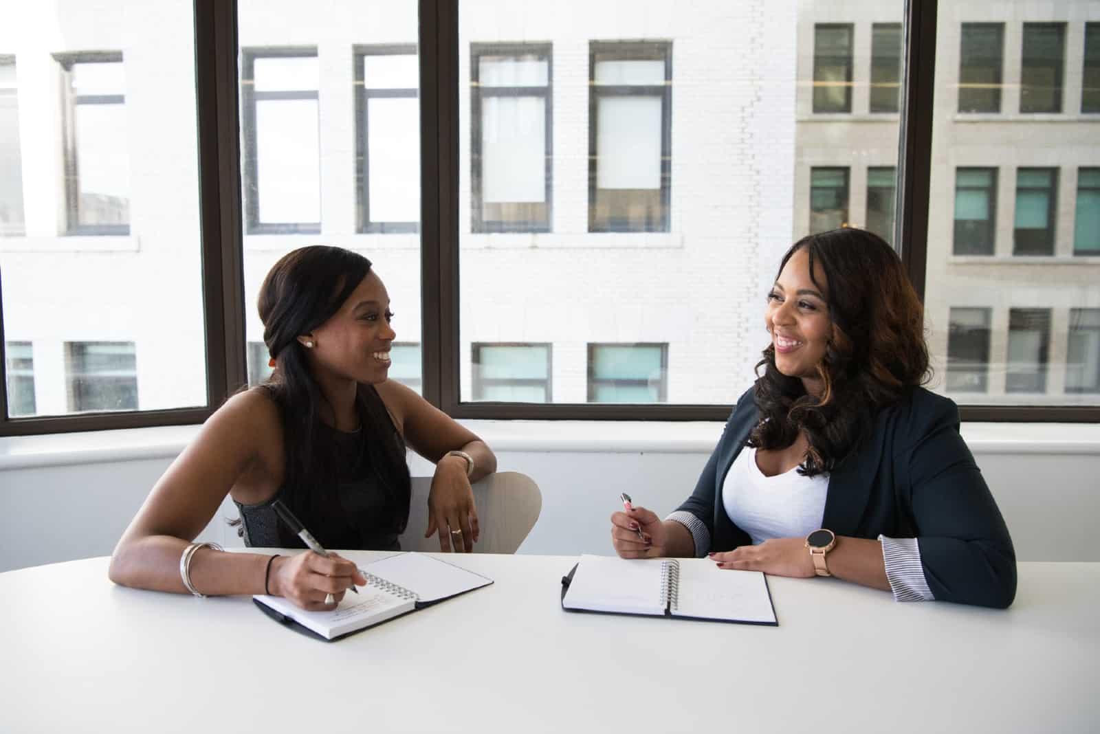 deux femmes souriantes assis au bureau