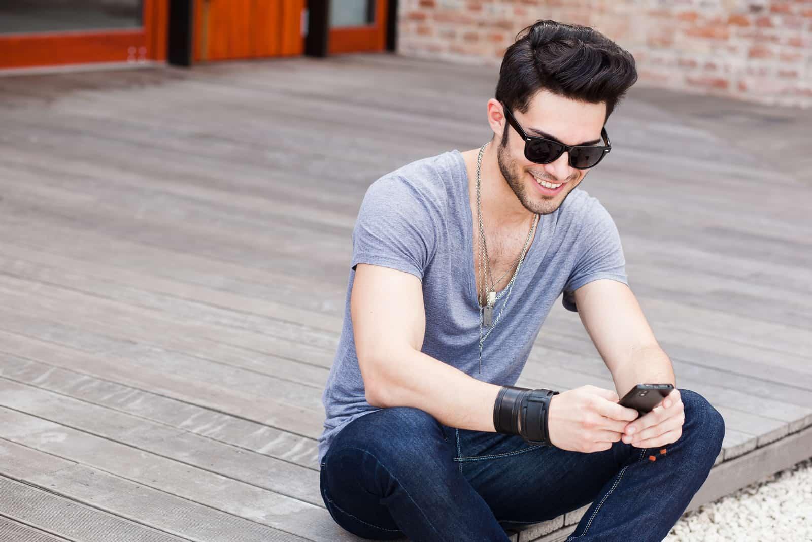 Homme avec des lunettes à l'aide de smartphone assis sur le sol