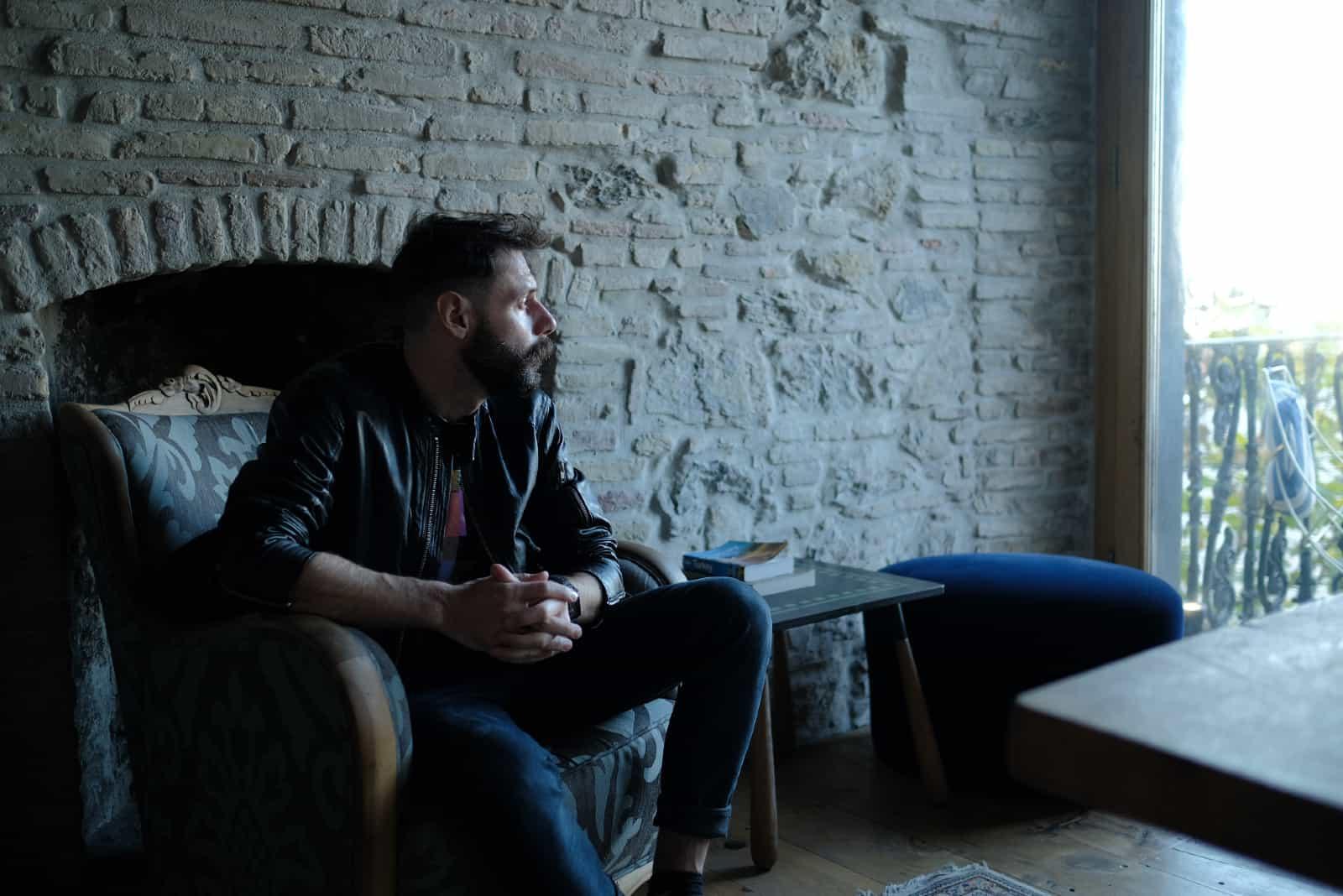 Homme pensif assis sur un fauteuil regardant à travers la fenêtre