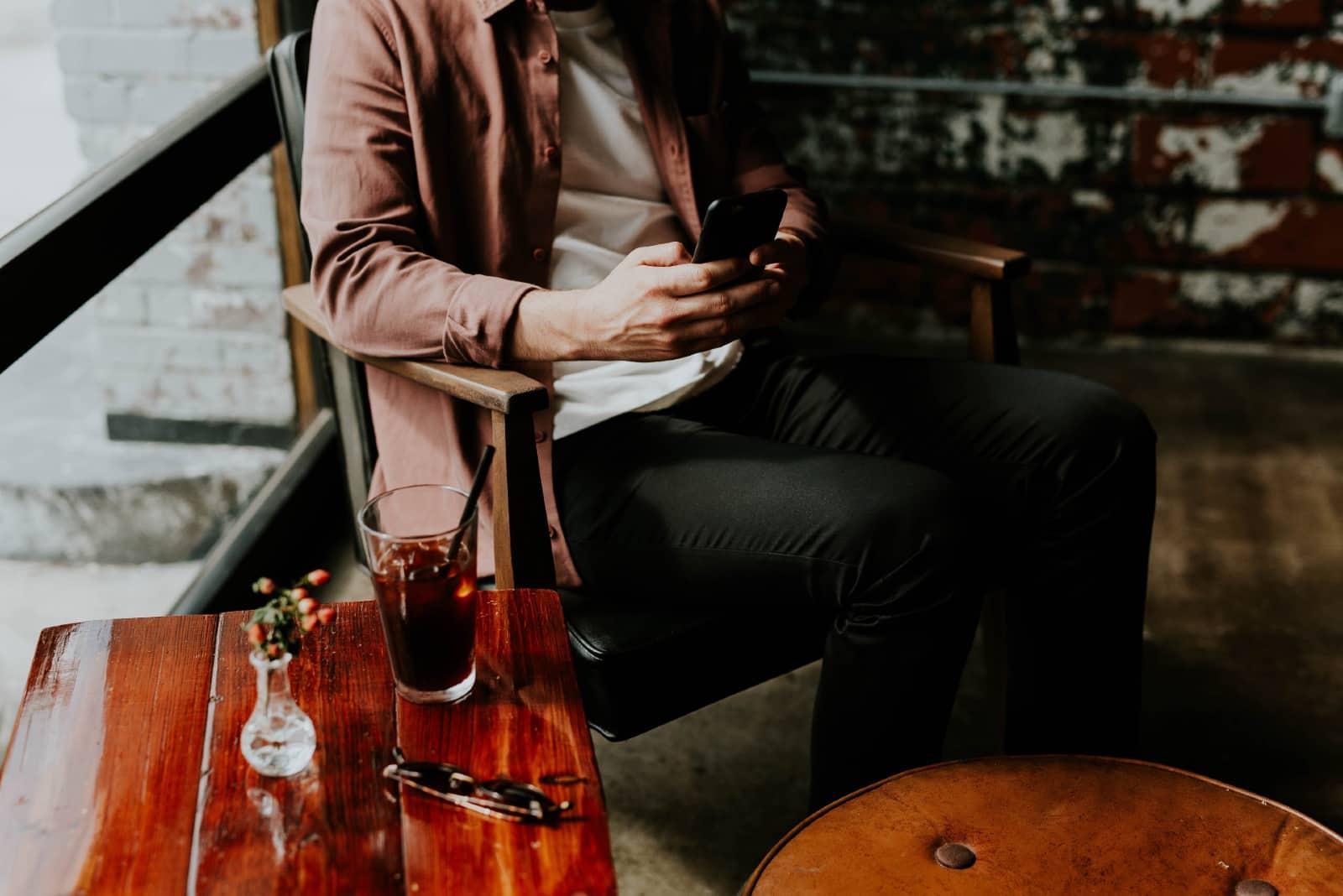 homme assis sur une chaise tout en utilisant un smartphone