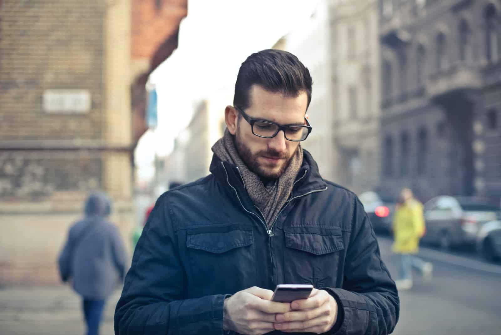 homme debout dans la rue regardant son smartphone