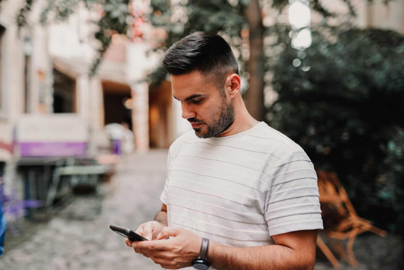 homme utilisant un smartphone en plein air
