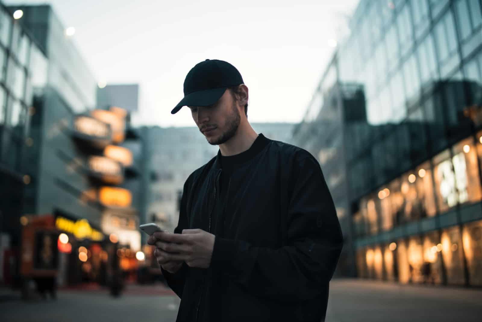 homme en veste noire à l'aide de smartphone en plein air