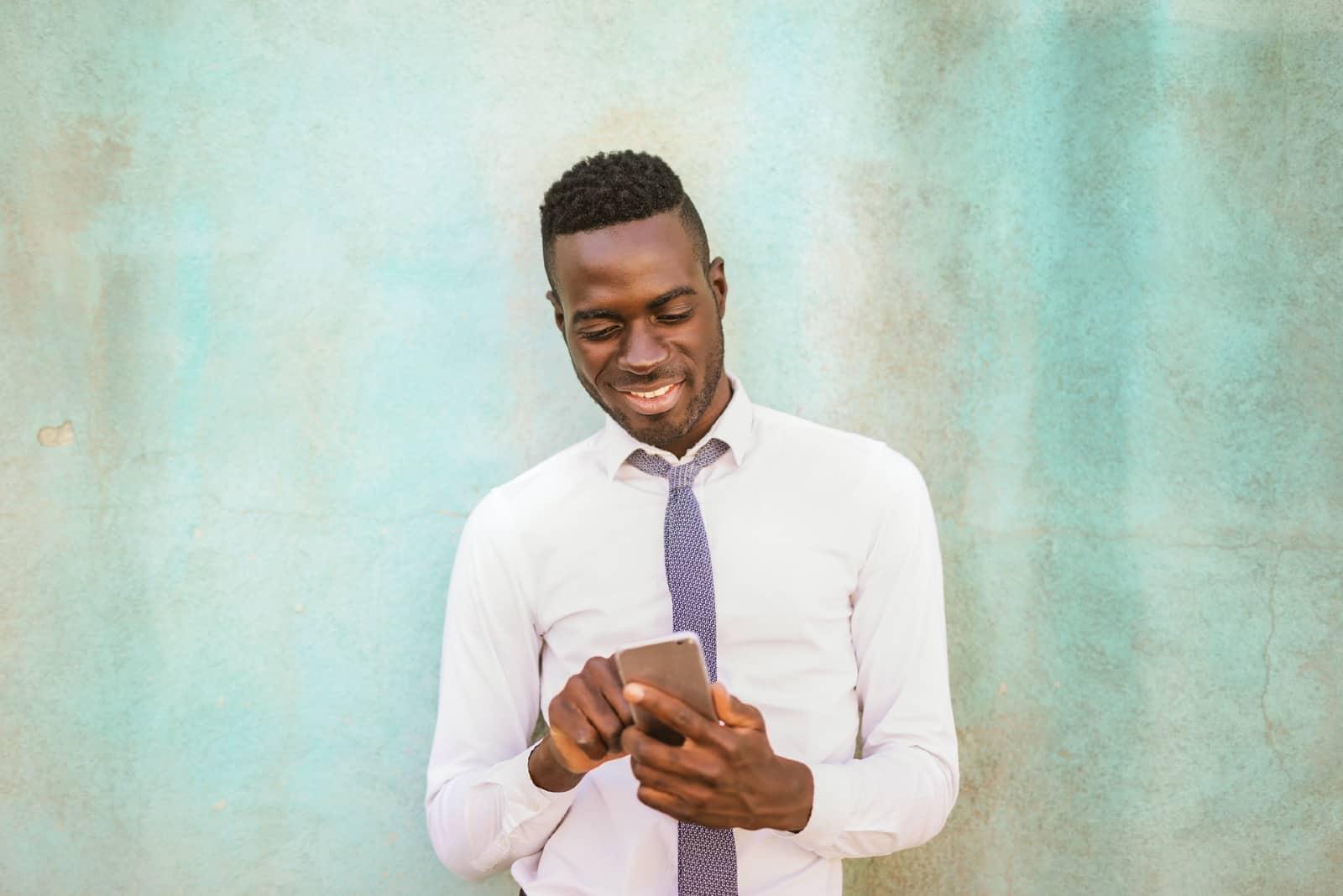 Homme debout près d'un mur, utilisant un smartphone