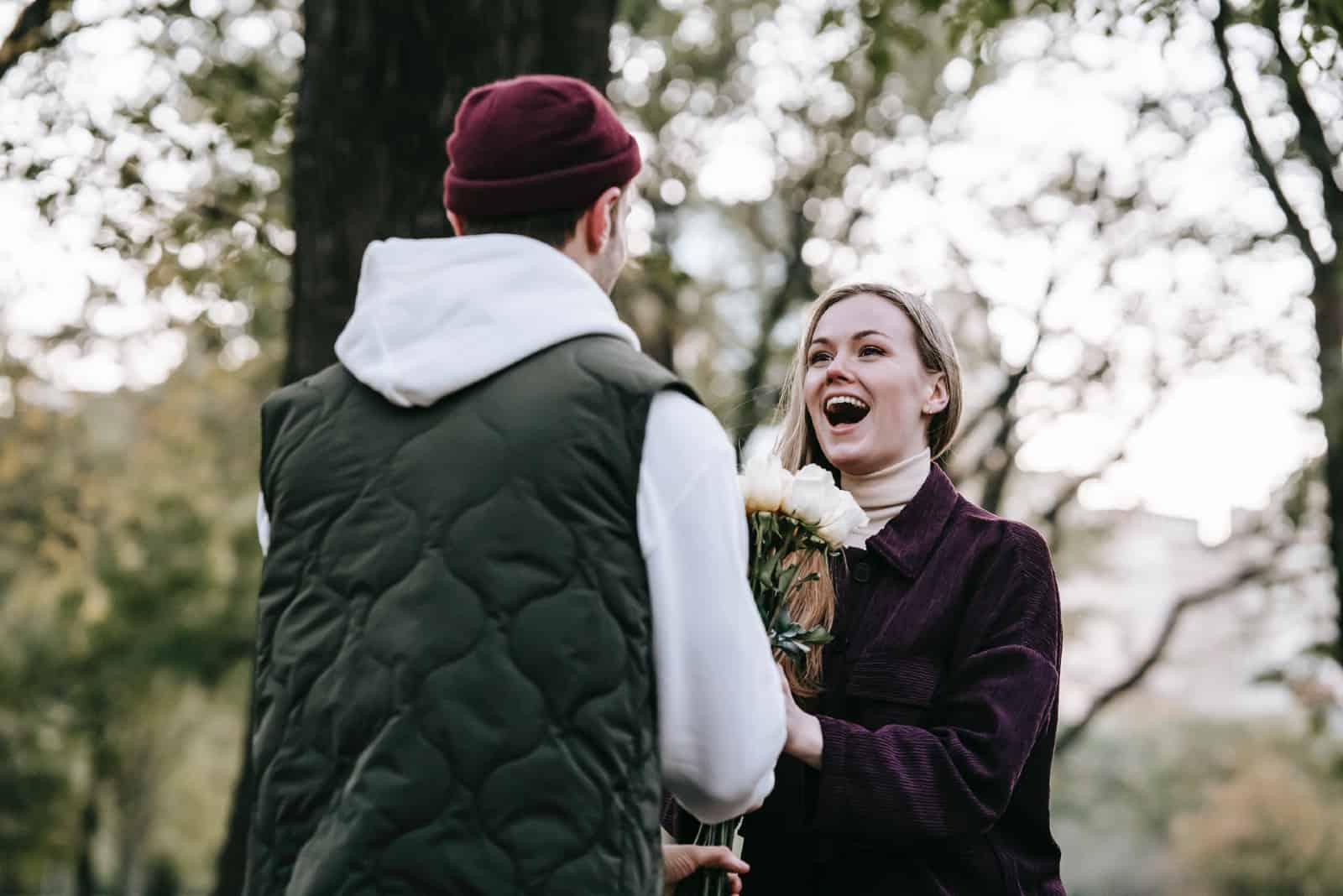 homme donnant un bouquet de fleurs à une femme en plein air
