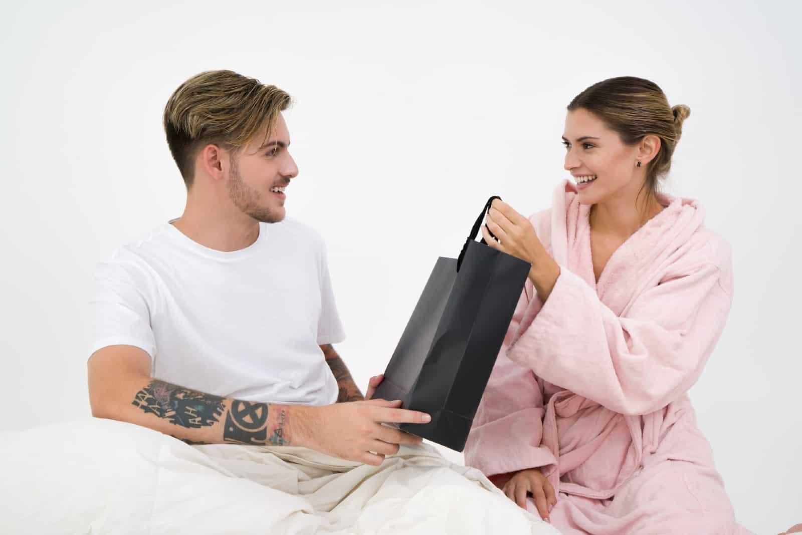 un homme donne un cadeau à une femme alors qu'il est assis près d'un mur