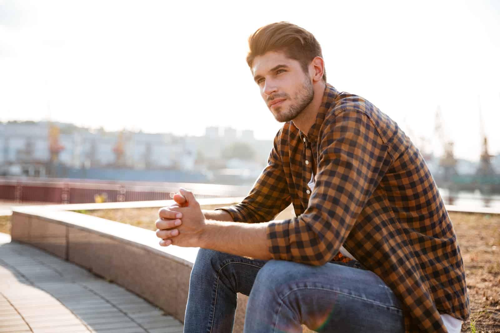 homme en chemise à carreaux réfléchissant tout en étant assis à l'extérieur
