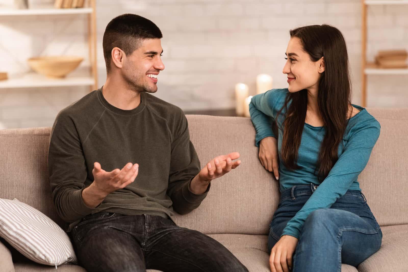 homme heureux parlant à une femme assise sur un canapé