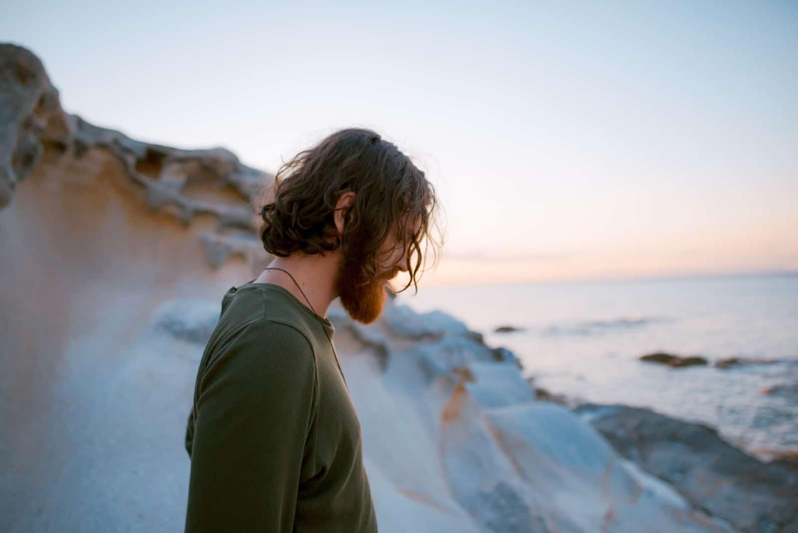 homme triste regardant vers le bas en se tenant debout près de la mer
