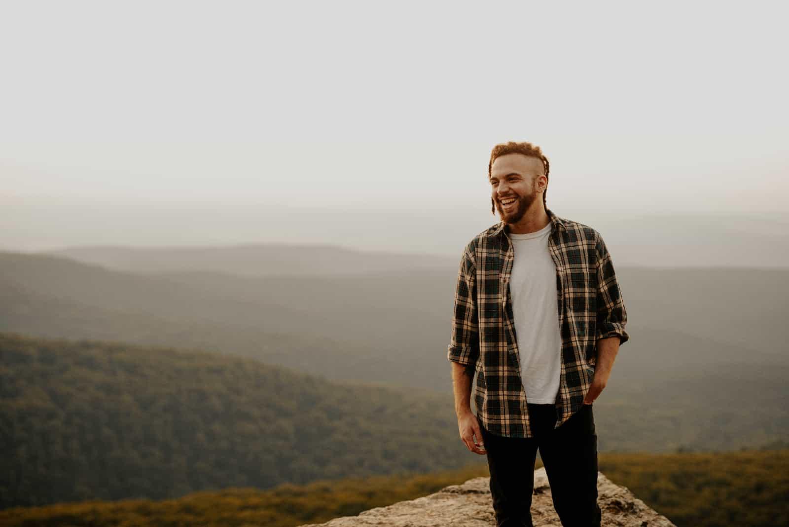 homme souriant au sommet d'une montagne