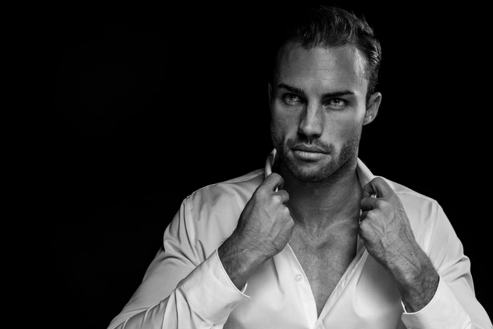 homme avec barbe touchant une chemise blanche