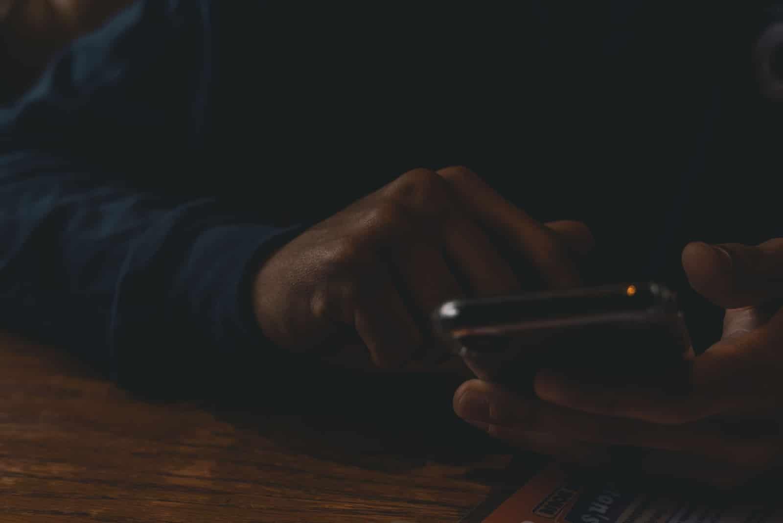 Homme utilisant un smartphone assis à une table