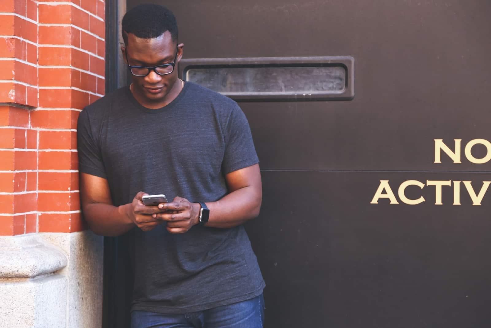 Un homme utilise un smartphone alors qu'il se tient près d'un mur de briques