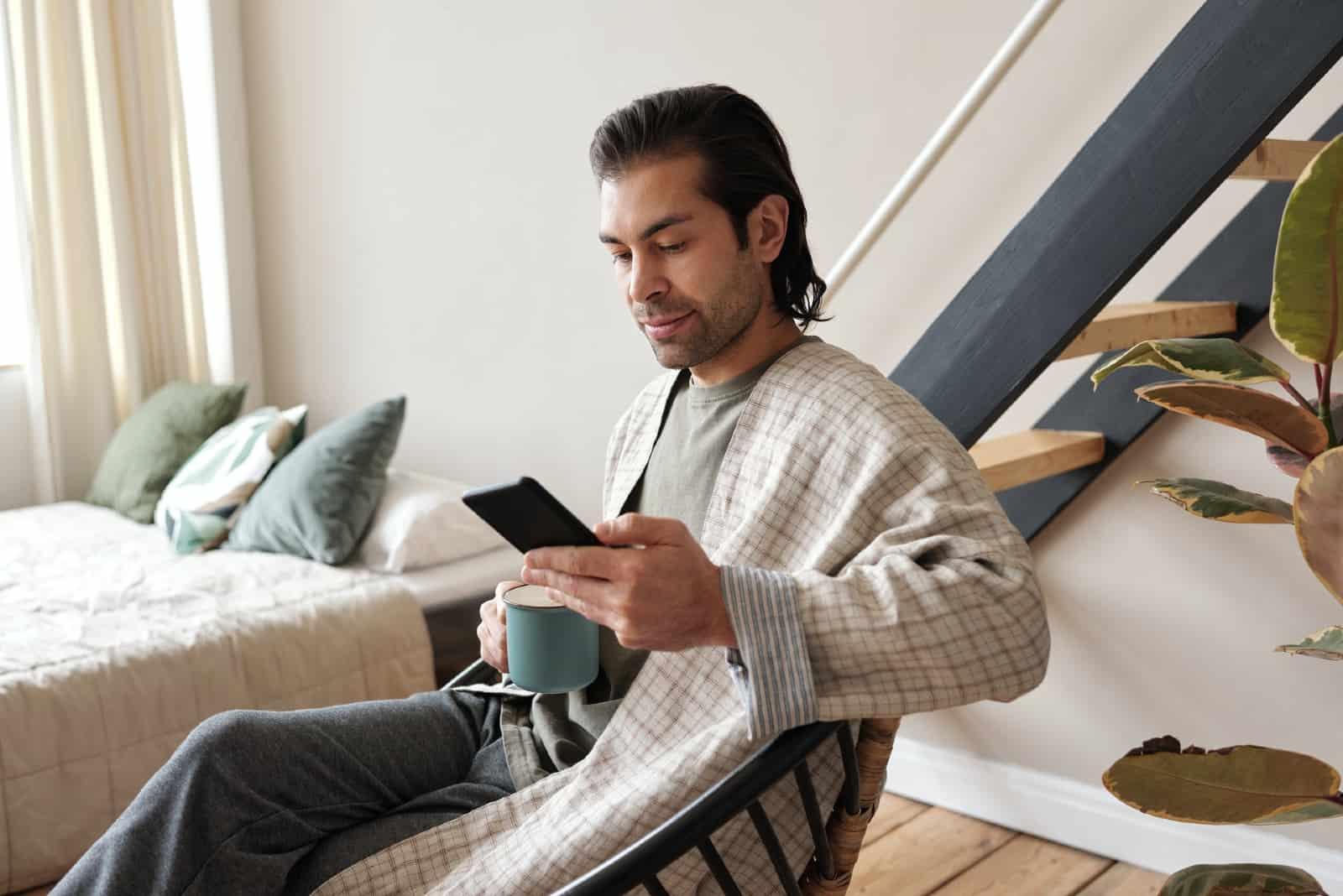 homme utilisant un smartphone tout en tenant une tasse verte