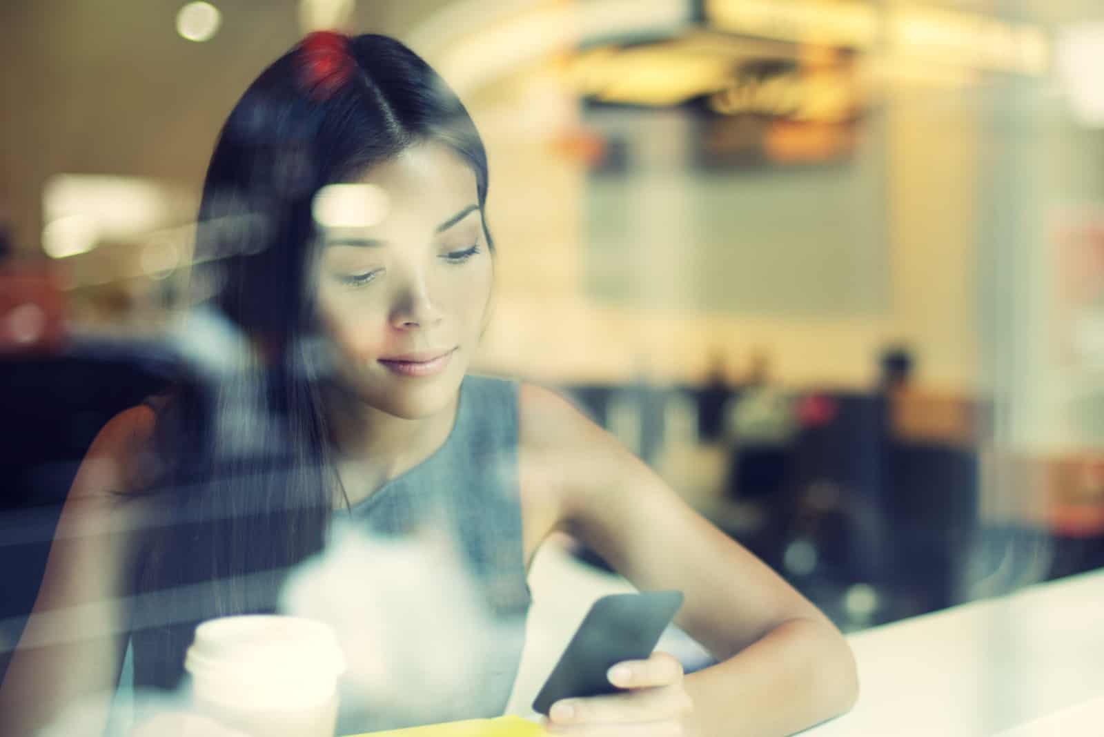 la femme est assise dans un café tenant un téléphone à la main