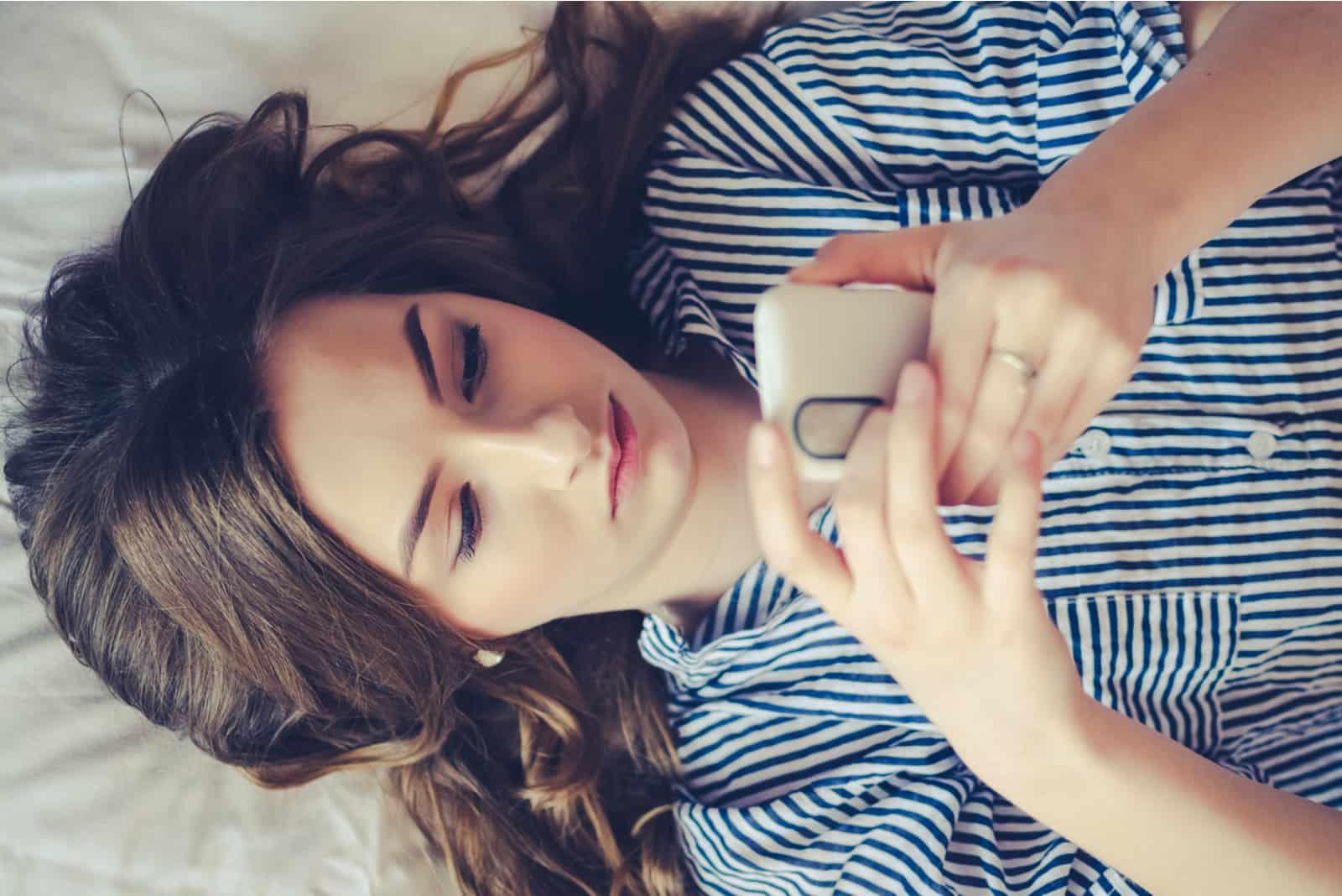 triste femme coucher lit et bouton téléphone