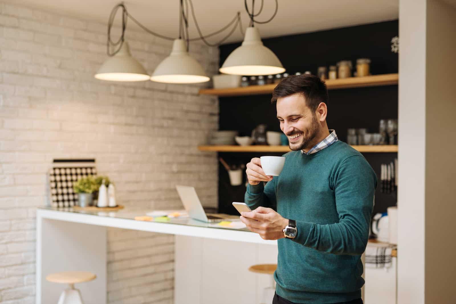 un homme est debout dans la cuisine, buvant du café et tenant un téléphone à la main