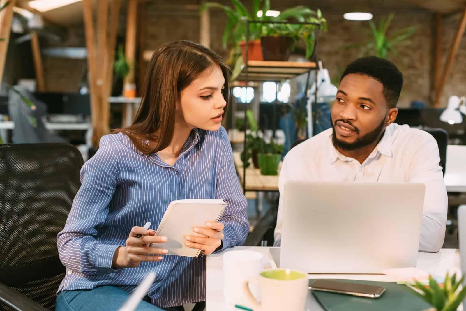 un homme et une femme s'assoient dans un café et parlent