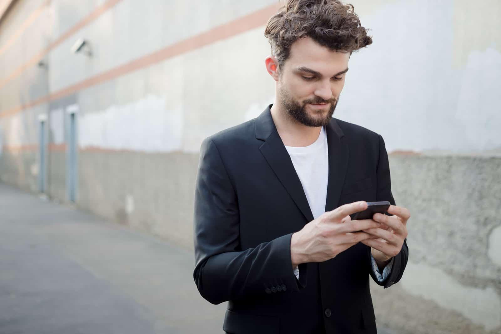 un homme se tient dans la rue et un bouton sur le téléphone