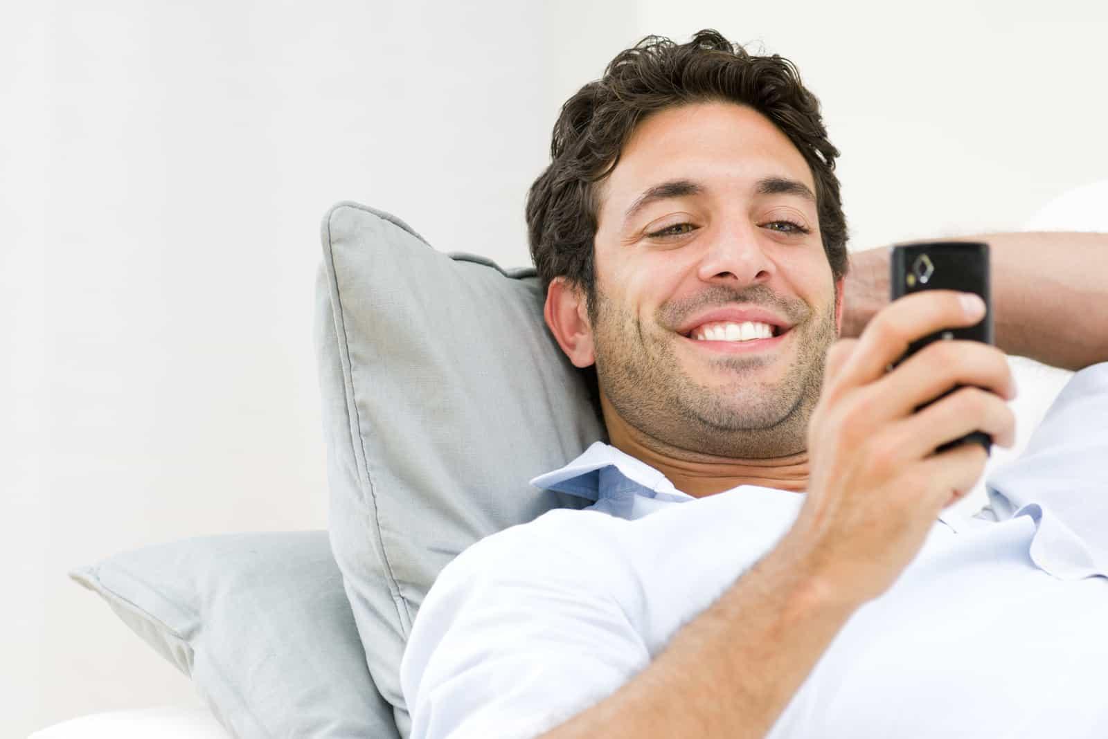un homme souriant se couche et les touches sur le téléphone