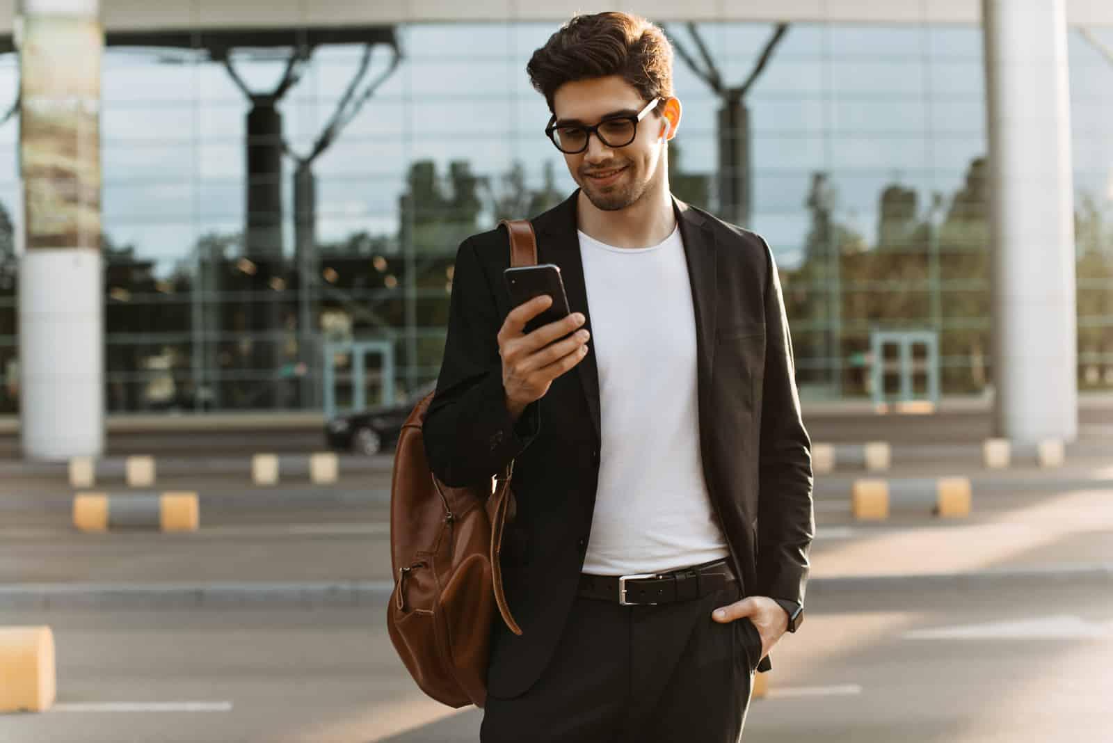 un homme souriant se tient dans la rue et les touches du téléphone