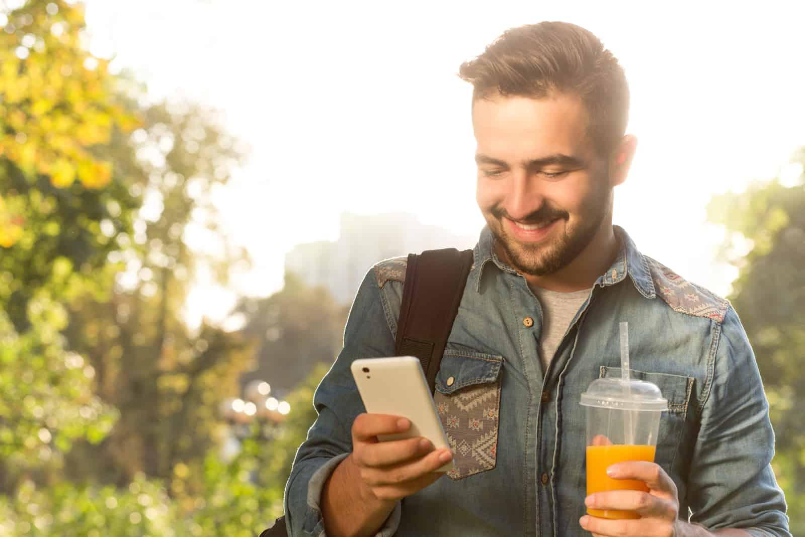 un homme souriant tient le jus dans sa main et frappe au téléphone