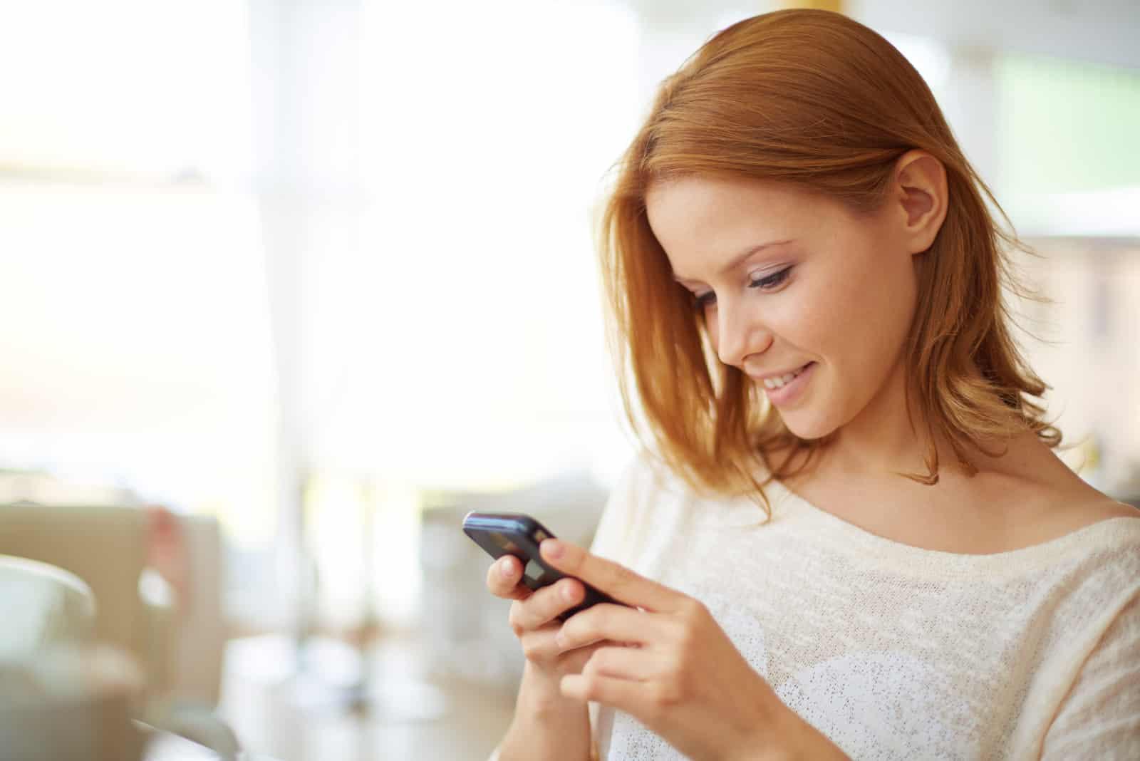 une femme aux cheveux bruns courts se dresse et des boutons sur le téléphone