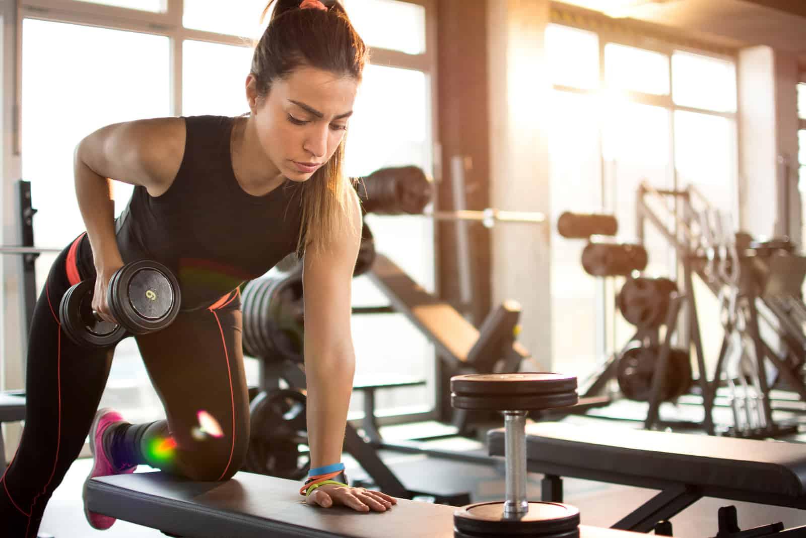 une femme soulève des poids au gymnase